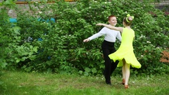 Young boy and girl in yellow dress dancing partner dance and smiling on grass Stock Footage
