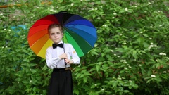 Girl in green dress coming and standing near boy with umbrella near bush. Stock Footage