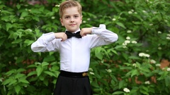 Boy adjusting bow tie and putting hands on hips Stock Footage