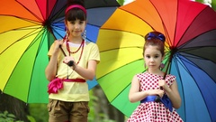 Two girl with umbrellas turning them, looking to each other and smiling. Stock Footage