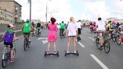 Back of two women on mini segway among bike riders Stock Footage