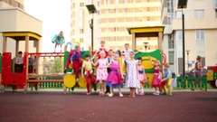Fourteen small girls and boys jumping from toy train, dancing and climbing Stock Footage