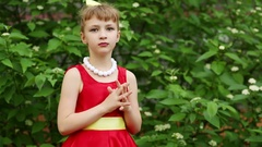 Girl in dress and face painting crossing fingers on chest and turning side Stock Footage