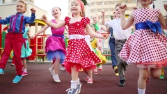 Fourteen small girls and boys energetic dancing on playground near houses. Stock Footage