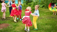 Six girls and boys twisting legs in pairs holding hands and small girl standing Stock Footage