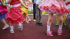 Legs of fourteen girls and boys energetic dancing twist on red playground. Stock Footage