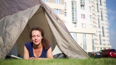 Woman in blue shirt lye and smile in tourist tent on lawn Stock Footage