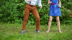 Legs of boy and girl in blue dress dancing on green grass. Stock Footage