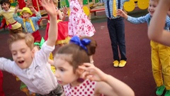 Fourteen small girls and boys in multi-color clothes raising arms and jumping Stock Footage