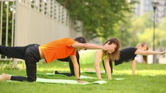 Man and two women on lawn perform yoga position on fours Stock Footage