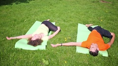 Man and two women perform yoga - lying with bended leg Stock Footage