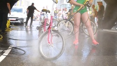 Woman in green shirt and shorts wash bike by Karcher machine near others Stock Footage