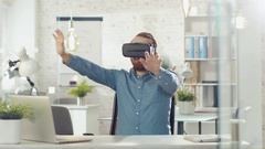 Creative Young Developer Uses Virtual Reality Glasses while Sitting at His Desk  Stock Footage