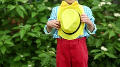 Hat in hands of boy in red trousers, checkered shirt and yellow bow tie Stock Footage