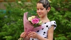 Girl in dress and hairdo in gel smelling bouquet of rose in hands Stock Footage