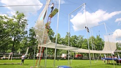 Woman waving on rope and another standing on platform near on trapeze Stock Footage