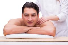 Handsome man during spa massaging session Stock Photos
