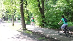 Bike riders going to Cycling Parade on street among tree Stock Footage