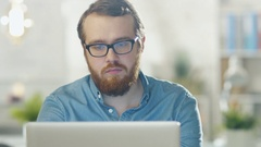 Portrait of a Bearded Young Man Wearing Glasses Sitting in His Office Working Stock Footage