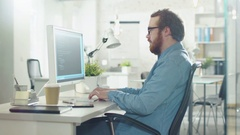 Bearded Creative Man Works on Code While Sitting at His Desk.  Stock Footage