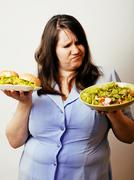 Fat white woman having choice between hamburger and salad close Stock Photos