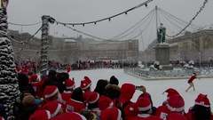 Crowd of Santa Clauses watching female Santa ice skating dance in new year snow Stock Footage