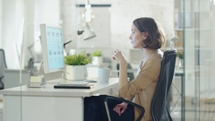 Creative Shorthaired Woman Works at Her Desk Thoughtfully. Sips Coffee. Stock Footage