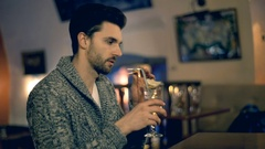 Handsome man in warm jumper drinking alcoholic beverage and smiling to the camer Stock Footage