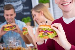 Man with cheeseburger smiling Stock Photos