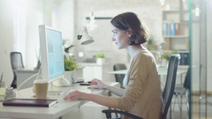 Young Beautiful Woman Works Sitting at Her Desk Using Personal Computer.  Stock Footage