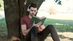 Man listening music while reading book in the park Stock Footage