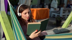 Absorbed girl listening music and reading book while sitting in hammock Stock Footage