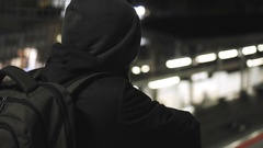 MIllenial youth in hoodie at the train station at night, slomo 100p Stock Footage