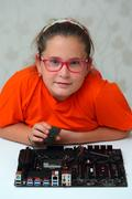 Little girl installs CPU to motherboard Stock Photos