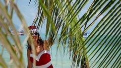 Young cute woman in santa hat look out from palm tree of branch on tropical Stock Footage