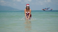 Young woman splashing the water on the beach in the sea in santa's hat and dress Stock Footage