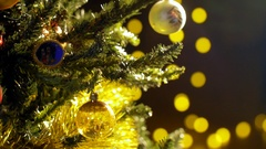 A woman hand is hanging a Christmas decoration to a branch of the Christmas tree Stock Footage