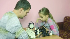 Dad and daughter in front of a game of chess greeted each other hands Stock Footage