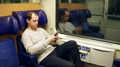 Man typing and scrolling app in his mobile phone in a train. Modern wireless Stock Footage