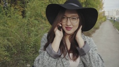 Young pretty woman in black hat and glasses calling to her friend outdoor Stock Footage