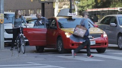 Man Getting Into a Cab at Rush Hour Stock Footage