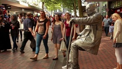 Street performer in Yoda costume seating on an invisible chair Stock Footage