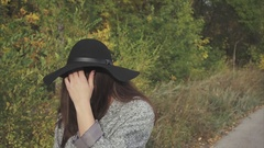 Portrait of young pretty smiling woman in black hat and glasses on autumn street Stock Footage