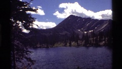 1972: a tranquil view of a river beneath a mountain HOLLAND LAKE MONTANA Stock Footage