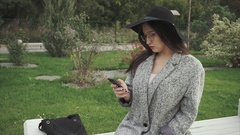 Pretty young woman in black hat and glasses using smartphone in city park Stock Footage