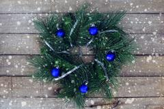 Christmas wreath on the wooden background with snow falling Kuvituskuvat