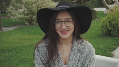 Close up portrait of pretty woman in black hat and glasses in the park outdoor Stock Footage