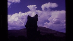 1972: natural formation tilts and reaches up toward blue sky and puffy cloud Stock Footage