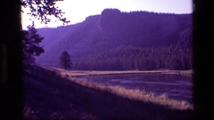 1972: river in forefront; trees and peaks behind IDAHO Stock Footage