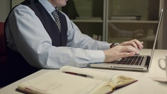 Handsome brunet man in suit and necktie typing on laptop computer at desk Stock Footage